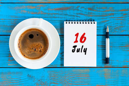 July 16th. Day 16 of month, calendar on blue wooden table background with morning coffee cup. Summer concept