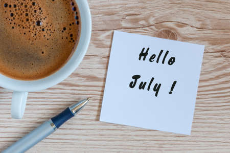 coming home: Hello July - message at home or office desk. With morning cup of coffee. Summer is Here concept
