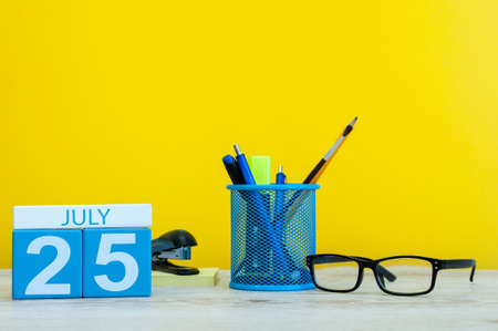 July 25th. Image of july 25, calendar on yellow background with office supplies. Summer time. With empty space for text Stock Photo