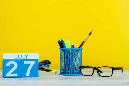 first day: July 27th. Image of july 27, calendar on yellow background with office supplies. Summer time. With empty space for text.