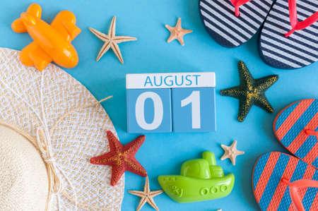 1 augustus. Afbeelding van 1 augustus kalender met zomer strand accessoires en reiziger outfit op achtergrond. Zomerdag, vakantieconcept