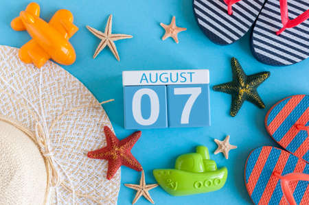 August 7th. Image of August 7 calendar with summer beach accessories and traveler outfit on background. Summer day, Vacation concept.