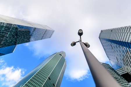 stylized banking: Photo of Streetlight or street lamp with blurred skyscrapers in background. Business center of the Moscow city concept.