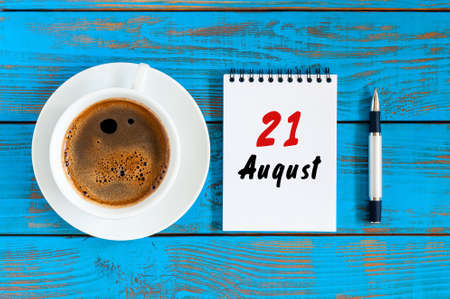 August 21st. Day 21 of month, daily calendar on blue background with morning coffee cup. Summer time. Unique top view