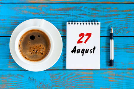 August 27th. Day 27 of month, daily calendar on blue background with morning coffee cup. Summer time. Unique top view Stock Photo