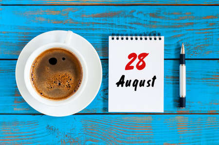 August 28th. Day 28 of month, daily calendar on blue background with morning coffee cup. Summer time. Unique top view Stock Photo