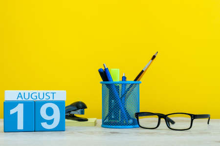 hi back: August 19th. Image of august 19, calendar on yellow background with office supplies. Summer time