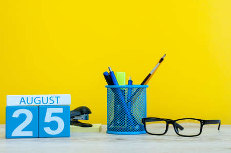 hi back: August 25th. Image of august 25, calendar on yellow background with office supplies. Summer time Stock Photo