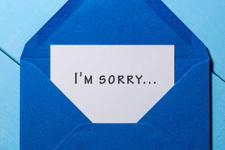 Lo siento - mensaje en el sobre azul en fondo de madera