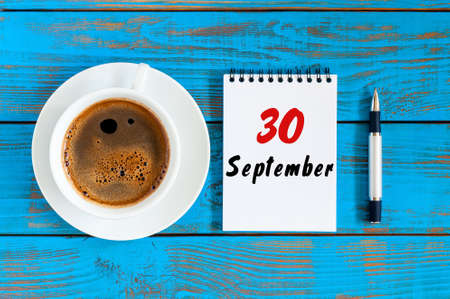 September 30th. Day 30 of month, loose-leaf calendar and hot cacao cup at translator or interpreter workplace background. Autumn time. Empty space for text