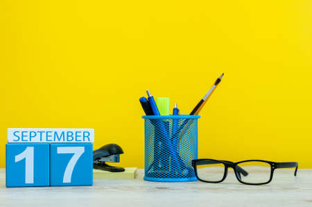 hi back: 17th September. Image of september 17, calendar on yellow background with office supplies. Fall, autumn time
