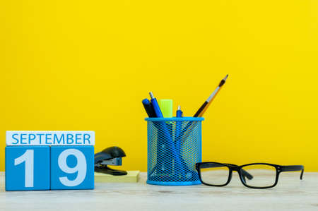 hi back: 19th September. Image of september 19, calendar on yellow background with office supplies. Fall, autumn time