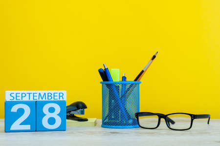 28th September. Image of september 28, calendar on yellow background with office supplies. Fall, autumn time