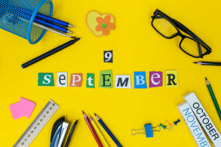 September 9th. Day 9 of month, Back to school concept. Calendar on teacher or student workplace background with school supplies on yellow table. Autumn time