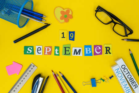 September 19th. Day 19 of month, Back to school concept. Calendar on teacher or student workplace background with school supplies on yellow table. Autumn time