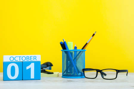 October 1st. Day 1 of month, wooden color calendar on teacher or student table, yellow background . Autumn time. Empty space for text