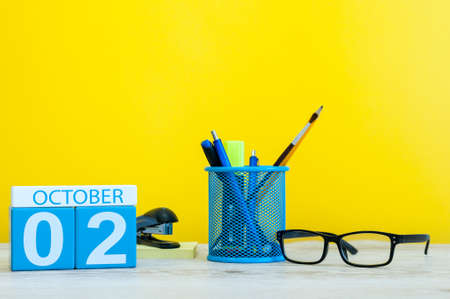 October 2nd. Day 2 of month, wooden color calendar on teacher or student table, yellow background . Autumn time. Empty space for text