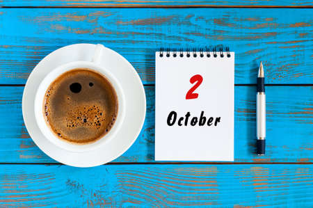 October 2nd. Day 2 of october month, calendar with hot coffee cup at blue table. Autumn time
