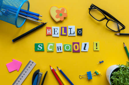 Hello School. Items for the school on a yellow table. Pupil outfit. Back to school concept Stock Photo