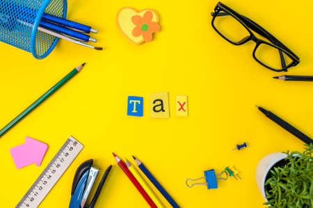 Time for Taxes. Money Financial Accounting. Taxation Concept with office suplies at yellow background Stock Photo