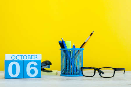 October 6th. Day 6 of month, wooden color calendar on teacher or student table, yellow background . Autumn time. Empty space for text