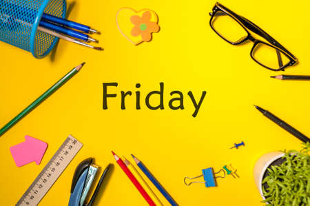 Friday on yellow table background with pencil, glasses and other office supplies. Business day concept Stock Photo