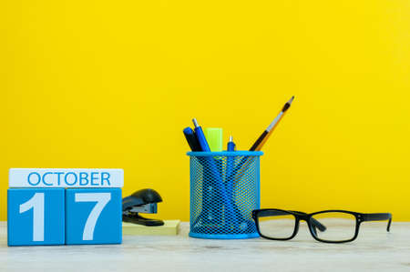 October 17th. Day 17 of october month, wooden color calendar on teacher or student table, yellow background . Autumn time