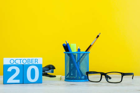 October 20th. Day 20 of october month, wooden color calendar on teacher or student table, yellow background . Autumn time