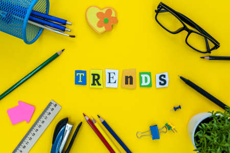 TRENDS - text of carved letters at yellow table background with office or pupil supplies
