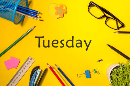 TUESDAY. Office supplies or student outfit on yellow table. Business creative consept, top view Stock Photo