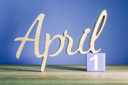 April 1st. Day 1 of month, calendar on wooden table and green background. Spring time, empty space for text Stock Photo