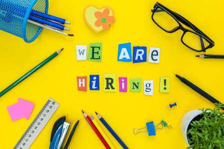 WE ARE HIRING CONCEPT ON yellow work place, office background with supplies Foto de archivo