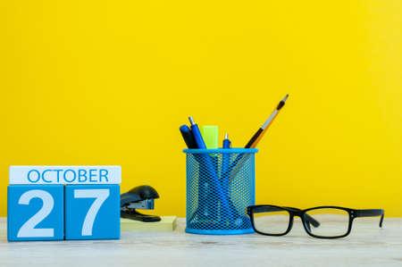 27 oktober. Dag 27 van oktober-maand, houten kleurenkalender op leraar of studententafel, gele achtergrond. Herfst tijd