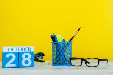 October 28th. Day 28 of october month, wooden color calendar on teacher or student table, yellow background . Autumn time
