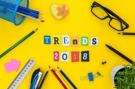 Trends 2018 - Text von geschnitzten Buchstaben am gelben Tabellenhintergrund mit Büro- oder Pupillenversorgungen. Neujahrsplan Standard-Bild - 87765650