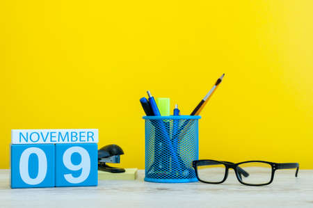November 9th. Day 9 of month, wooden color calendar on yellow background with office supplies. Autumn time