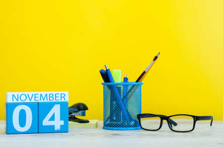 important date: November 4th. Day 4 of month, wooden color calendar on yellow background with office supplies. Autumn time Stock Photo