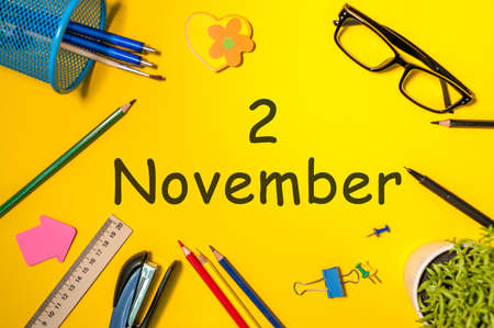 November 2nd. Day 2 of last autumn month, calendar on yellow background with office supplies. Business theme.