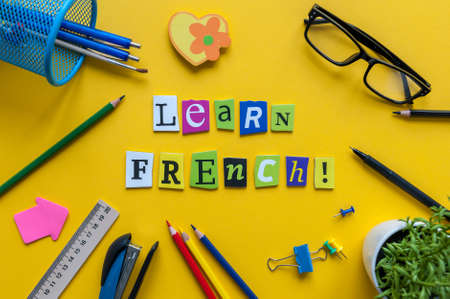 Word LEARN FRENCH made with carved letters on yellow desk with office or school supplies, stationery. Concept of Franch language courses.