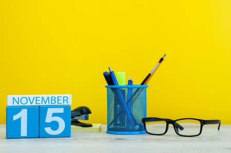 important date: November 15th. Day 15 of month, wooden color calendar on yellow background with office supplies. Autumn time