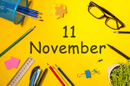 calendario noviembre: November 11th. Day 11 of last autumn month, calendar on yellow background with office supplies. Business theme