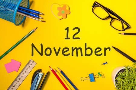 November 12th. Day 12 of last autumn month, calendar on yellow background with office supplies. Business theme