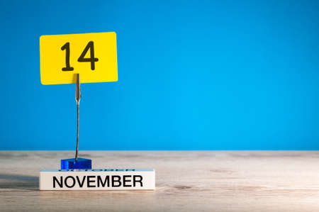 November 14th. Day 14 of november month, calendar on workplace with blue background. Autumn time. Empty space for text