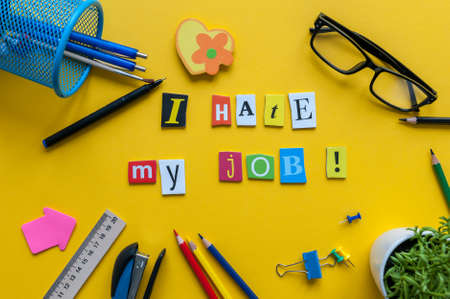 Workplace with I Hate My Job sign of carved letters and office supplies on yellow background Stock Photo