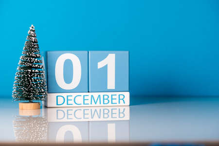 December 1st. Day 1 of december month, calendar with little christmas tree on blue background. Winter time.