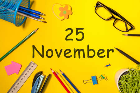 November 25th. Day 25 of last autumn month, calendar on yellow background with office supplies. Business theme