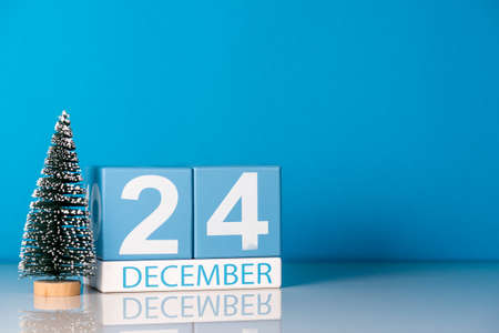 Eve Christmas. December 24th. Day 24 of december month, calendar with little christmas tree on blue background. Winter time. Empty space for text. New year concept Stock Photo