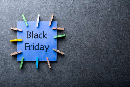 a blue paper label with the text black friday written in it against a dark gray background. Day with biggest Sale. Mockup Stock fotó
