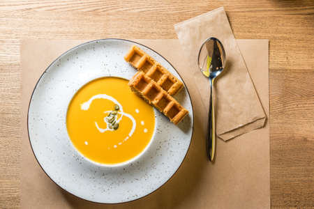 A bowl of spicy pumpkin soup with Belgian waffles. Traditional autumn food. Photo from home kitchen or family cafe Stockfoto