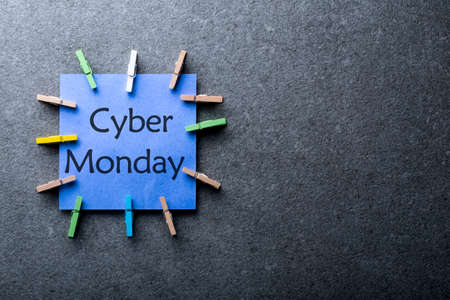 Online shopping concept. A blue paper label with the text Cyber Monday written in it against a dark gray background. Day with biggest Sale. Mockup